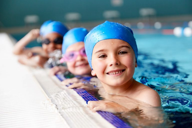 A group of children are in the pool ready for swimming lessons