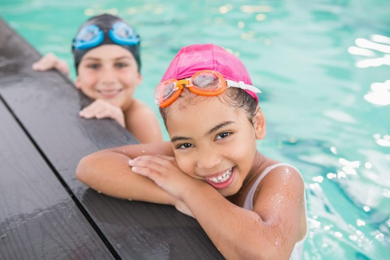 Two young girls look happy in a swimming pool