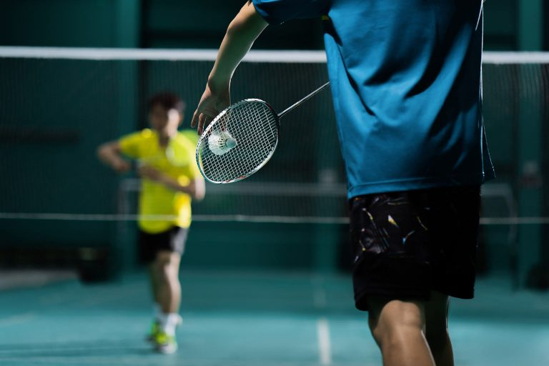 A man prepares to serve in an indoor badminton game