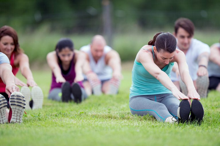 A group of people stretch outside for a boot camp