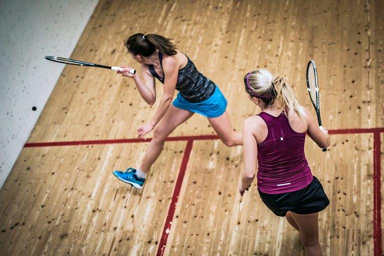 Two women play squash