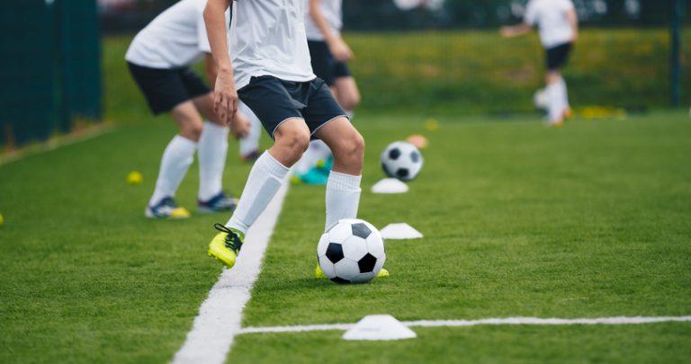 Boys Kicking Soccer Balls on Practice Session